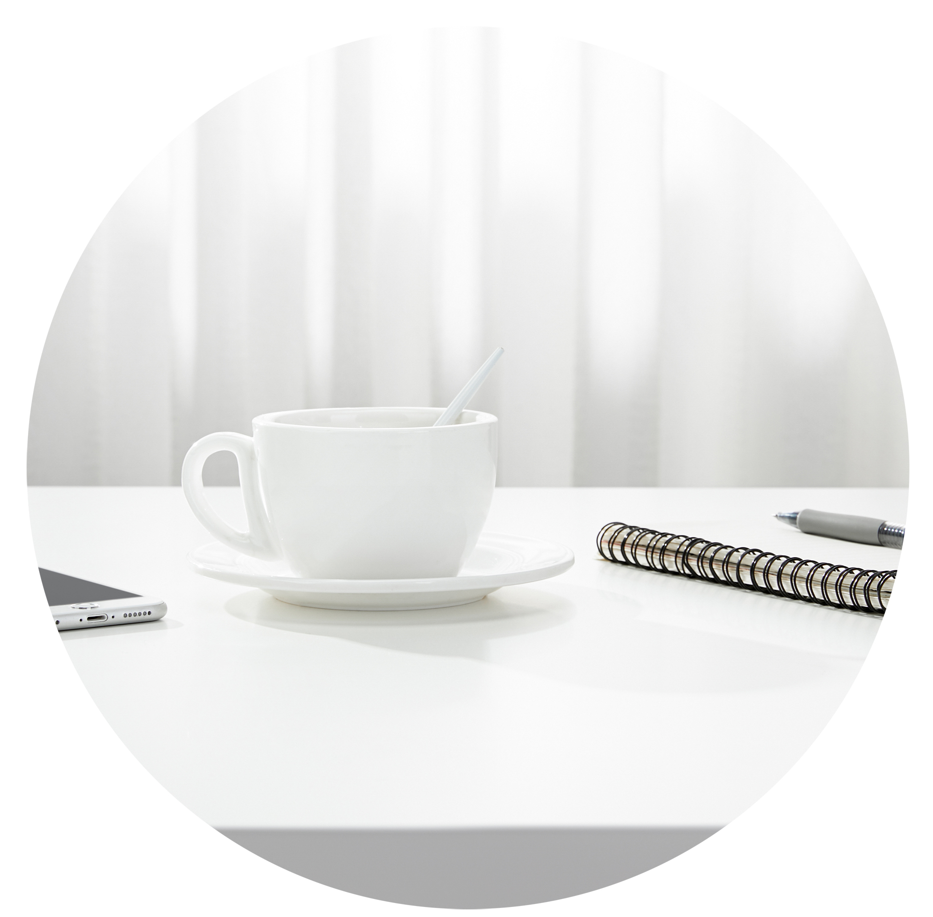 A closeup of a cup of coffee, a notebook and pen, and a smartphone on a white desk, indoors